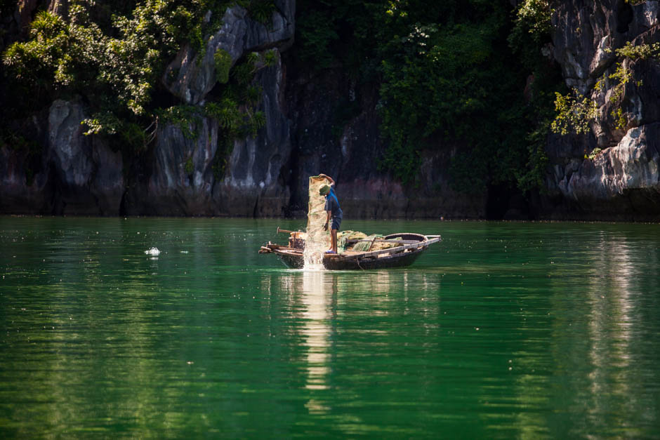 Halong bay vietnam photo of a Vietnamese man fishing.